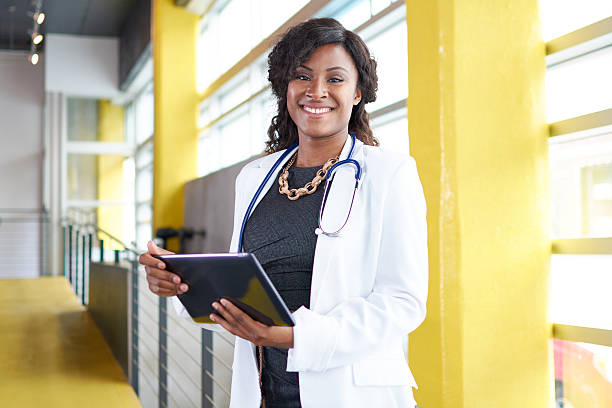 Portrait of a female doctor holding her patient chart on Friendly and attractive of a african american woman practitioner standing in a glass hall office of the clinic and examining documents director stock pictures, royalty-free photos & images