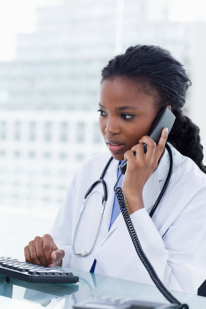 portrait of a female doctor using her computer - nurse on phone stock photos and pictures