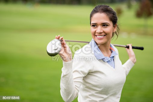Portrait of a female golfer holding the golf club at the course and smiling - sports training concepts