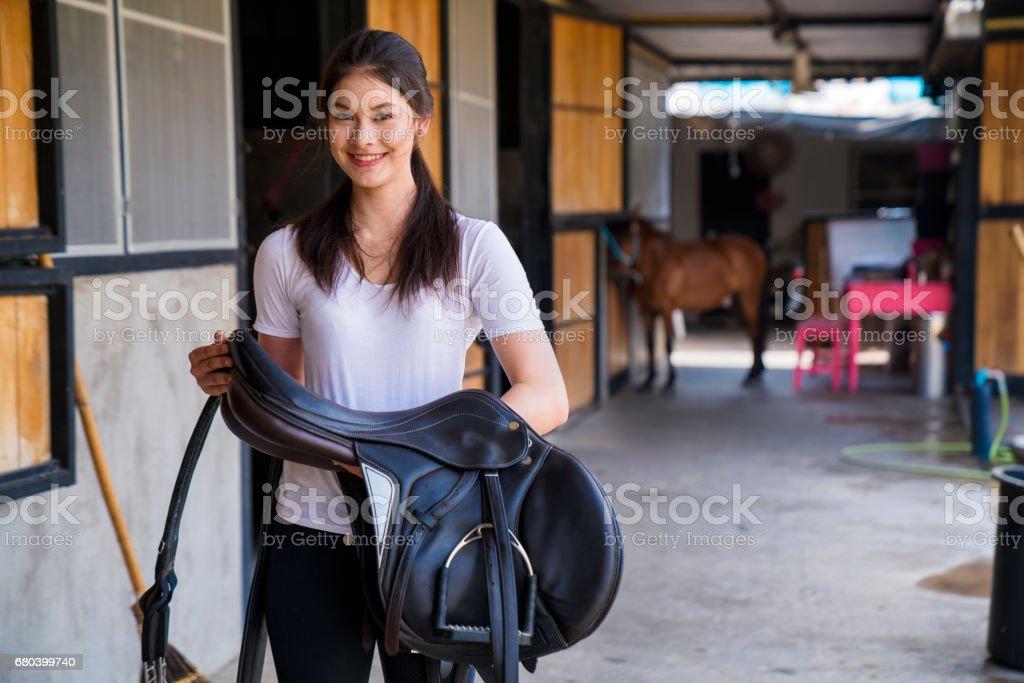 Portrait of a female horse rider holding a horses saddle stock photo