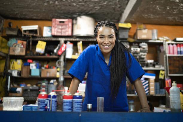 portret van een vrouwelijke monteur staande achter de balie in een auto repair shop - kas bouwwerk stockfoto's en -beelden