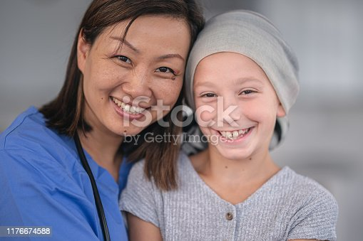 1041630080istockphoto Portrait of a female nurse comforting a girl with cancer 1176674588