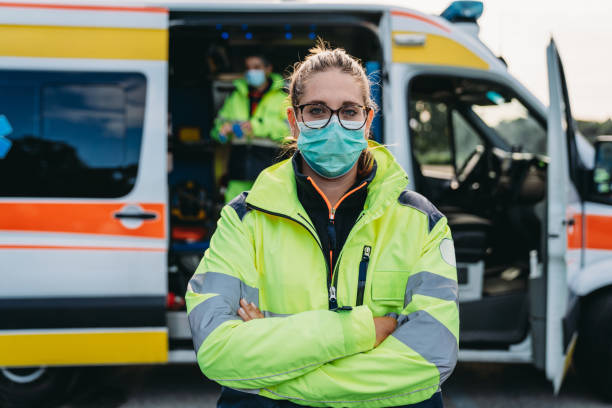 Portrait of a female paramedic in front of an ambulance outdoor stock photo