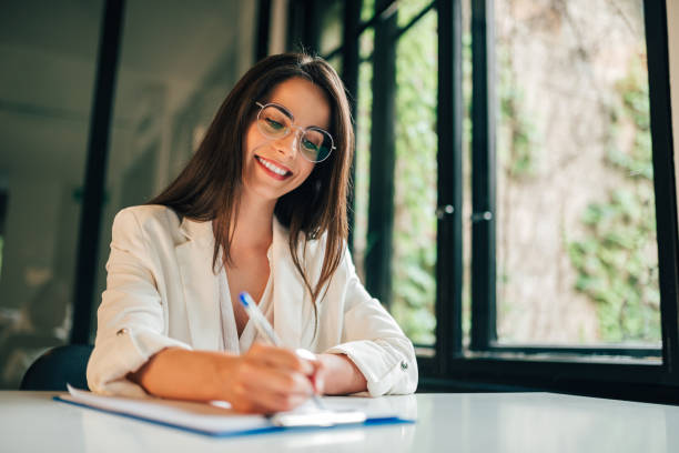 porträt einer studentin, die den fragebogen ausfüllt, während sie an der universität am schreibtisch sitzt. - weibliche führungskraft stock-fotos und bilder