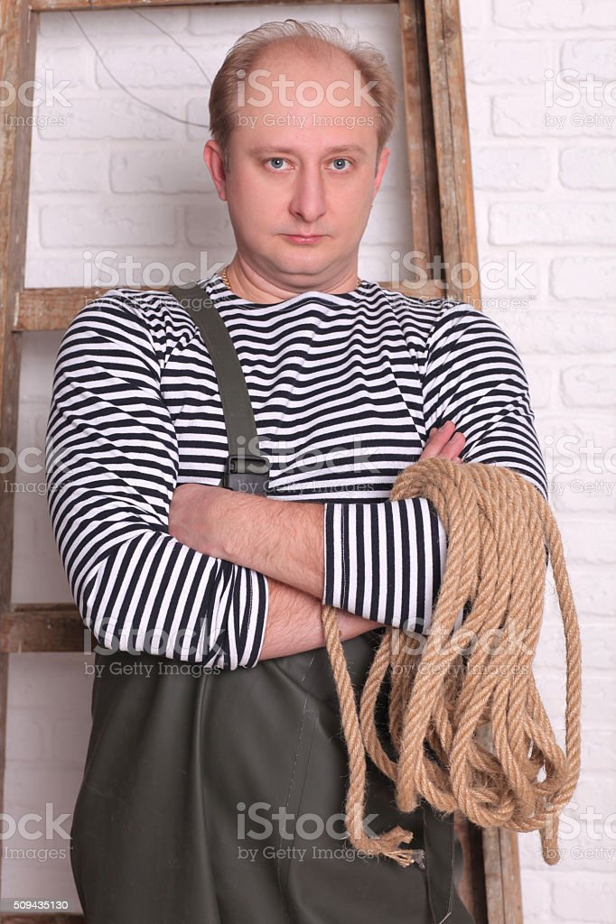 Portrait of a fisherman in waders with rope stock photo