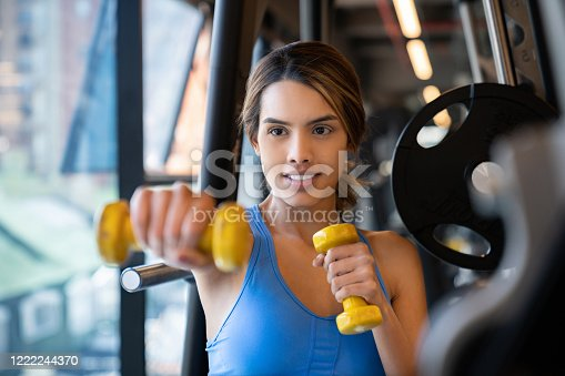 Portrait of a young fit woman exercising at the gym using free-weights – fitness concepts