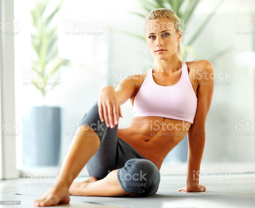 Portrait of a fit young female sitting on floor royalty-free stock photo