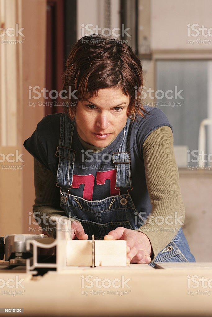 Portrait of a focused female carpenter hard at work royalty-free stock photo