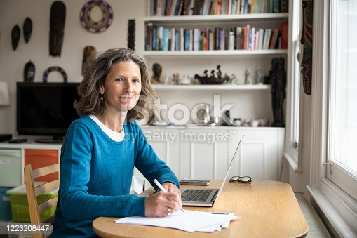 Mature caucasian female freelancer sitting at desk in living room