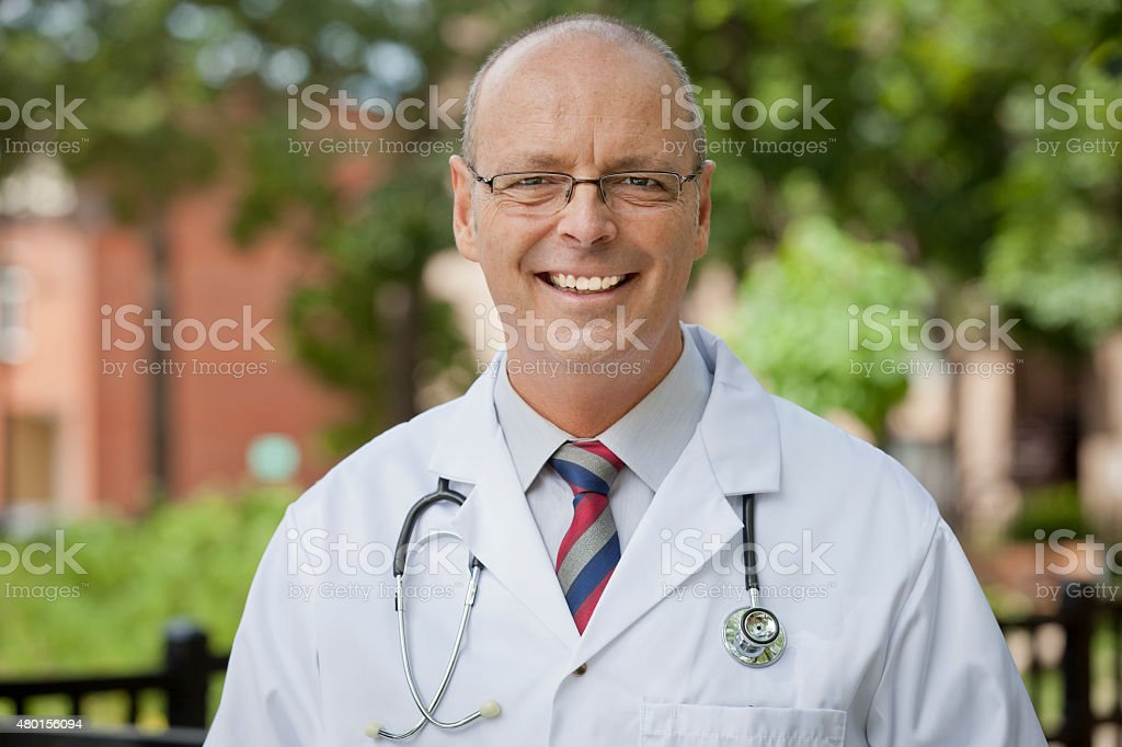 Portrait Of A Friendly Doctor Smiling At The Camera stock photo