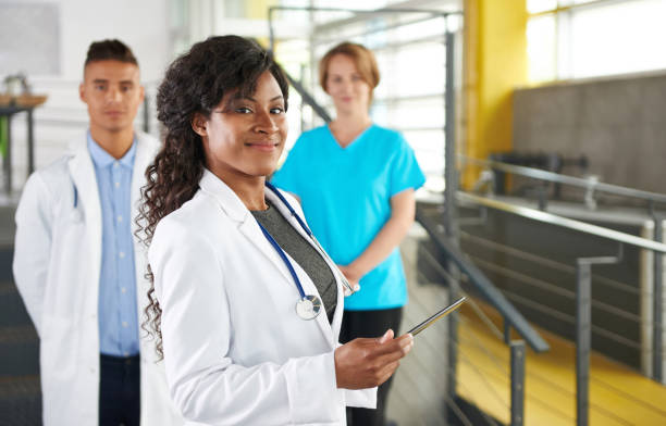 Portrait of a friendly female african american doctor and team in bright modern office stock photo