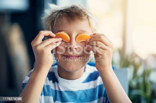 Little boy is eating orange. He is holding orange carpels as his eyes. Nikon D850