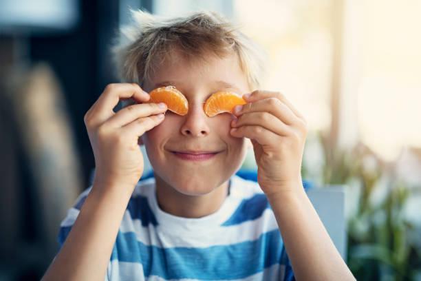 porträtt av en rolig liten pojke äta orange - carpel bildbanksfoton och bilder
