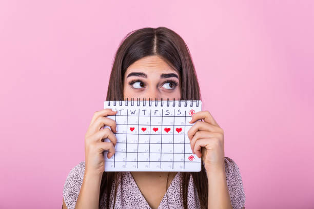 portrait of a funny young girl in hiding behind a menstrual periods calendar and looking away at copy space isolated over pink background. female period calendar - mestruazione foto e immagini stock