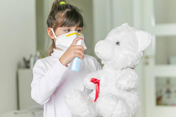Porträt eines Mädchens, das ihren Teddybären reinigt, eine Schutzmaske mit Handdesinfektionsmittel – Foto