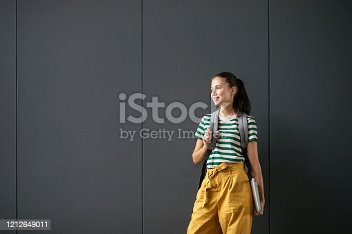 Portrait of beautiful Caucasian girl college student standing by the grey wall with backpack.