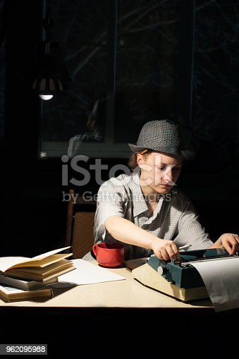 158326970 istock photo Portrait of a girl in a hat sitting at a table and typing on a typewriter at night 962095988