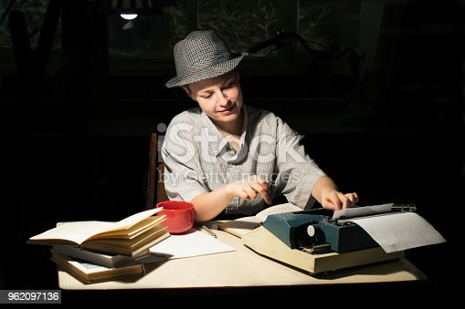 158326970 istock photo Portrait of a girl in a hat sitting at a table and typing on a typewriter at night 962097136