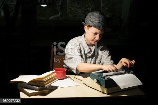 158326970 istock photo Portrait of a girl in a hat sitting at a table and typing on a typewriter at night 962097232