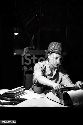 158326970 istock photo Portrait of a girl in a hat sitting at a table and typing on a typewriter at night 962097362