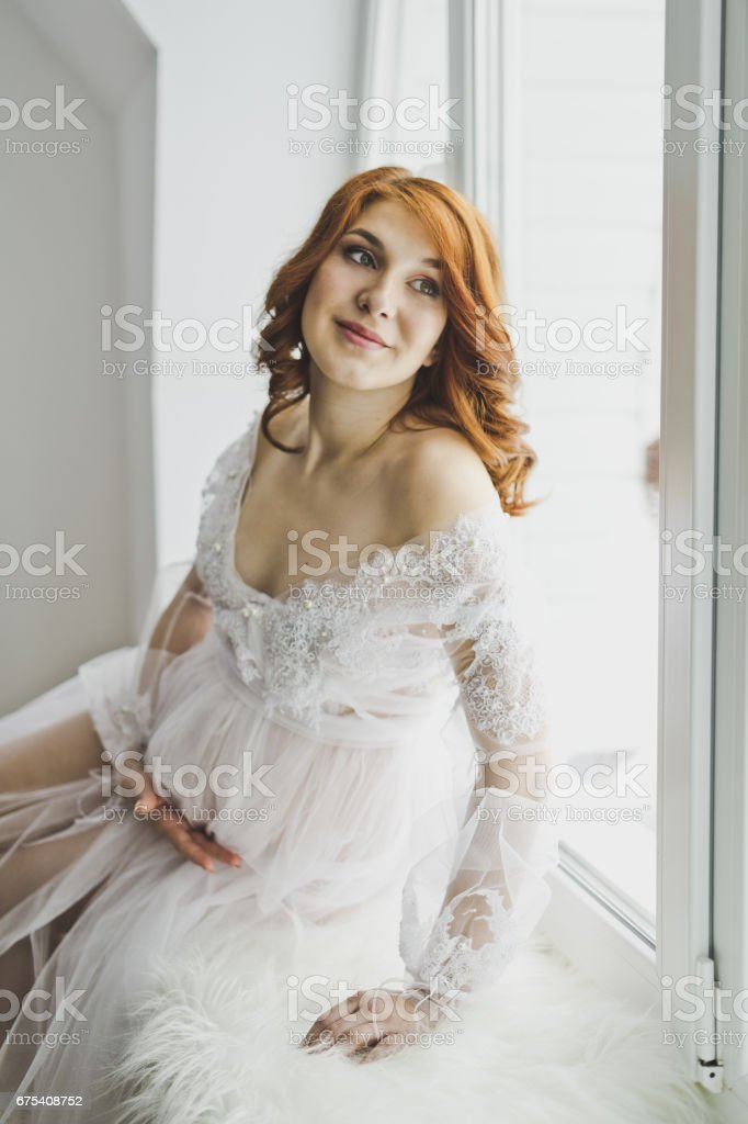 Portrait of a girl in the position of sitting at the bright window 6878. royalty-free stock photo