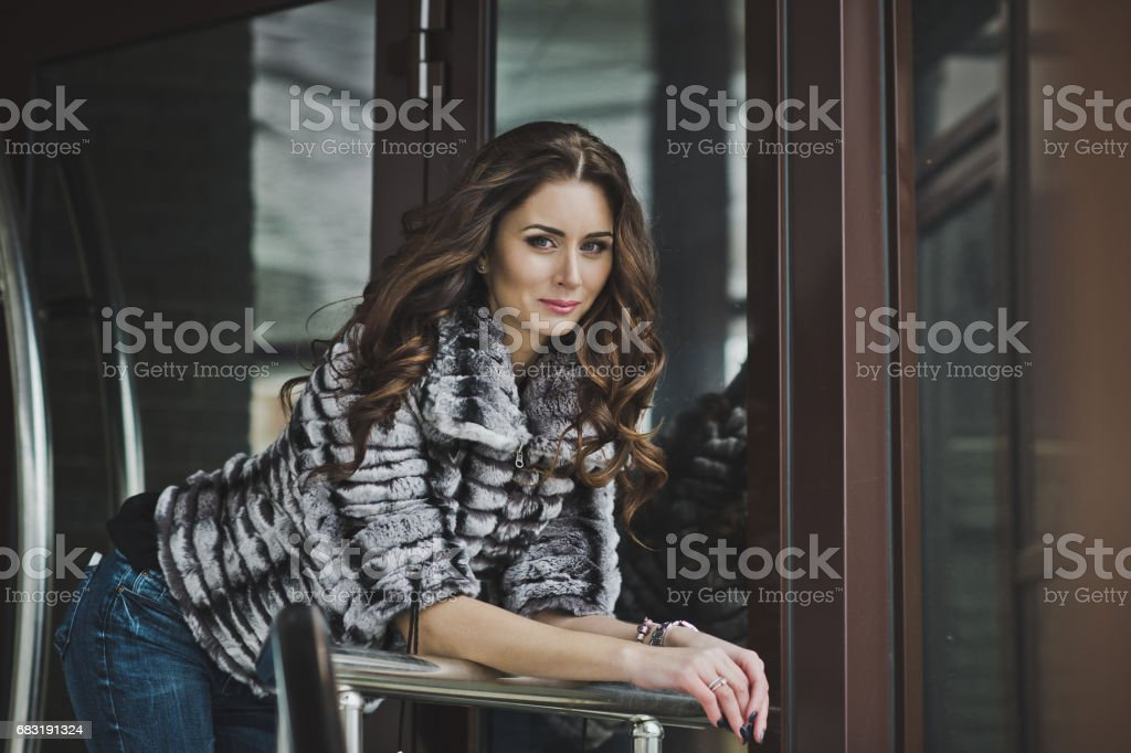 Portrait of a girl in winter clothes front of the building 4996. 免版稅 stock photo