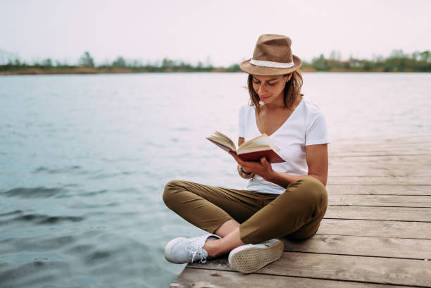Portrait of a girl reading a book while sitting on a small wooden wharf. stock photo