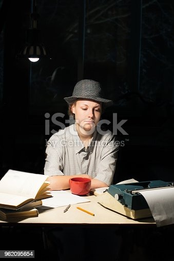 158326970 istock photo Portrait of a girl sitting at a table with a typewriter and books, think about the idea at night 962095654