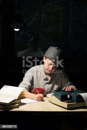158326970 istock photo Portrait of a girl sitting at a table with a typewriter and books, making notes at night 962095774