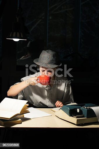 158326970 istock photo Portrait of a girl sitting at a table with a typewriter and books, drinking tea at night 962095868