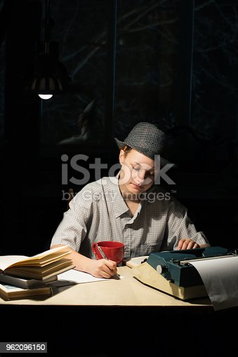158326970 istock photo Portrait of a girl sitting at a table with a typewriter and books, making notes at night 962096150