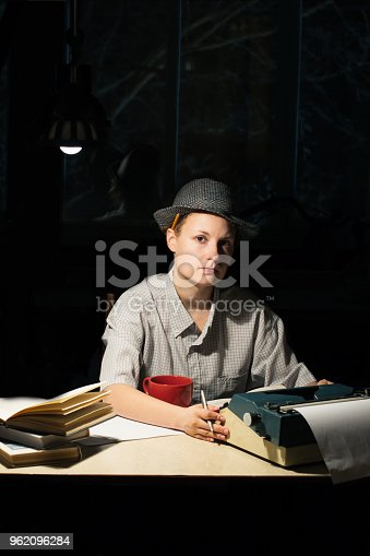 158326970 istock photo Portrait of a girl sitting at a table with a typewriter and books, think about the idea at night 962096284