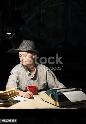 158326970 istock photo Portrait of a girl sitting at a table with a typewriter and books, making notes at night 962096394