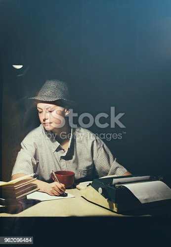158326970 istock photo Portrait of a girl sitting at a table with a typewriter and books, making notes at night 962096484