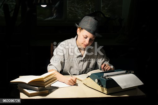 158326970 istock photo Portrait of a girl sitting at a table with a typewriter and books, making notes at night 962096726