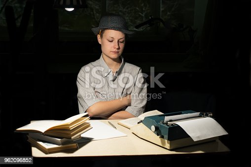 158326970 istock photo Portrait of a girl sitting at a table with a typewriter and books, think about the idea at night 962096852