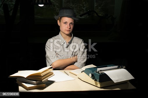 158326970 istock photo Portrait of a girl sitting at a table with a typewriter and books, think about the idea at night 962096936