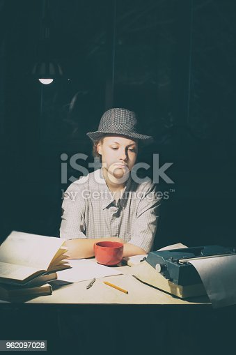 158326970 istock photo Portrait of a girl sitting at a table with a typewriter and books, think about the idea at night 962097028