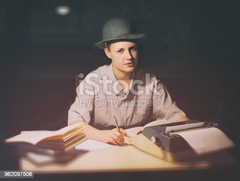158326970 istock photo Portrait of a girl sitting at a table with a typewriter and books, think about the idea at night 962097506