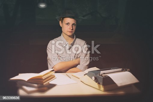 158326970 istock photo Portrait of a girl sitting at a table with a typewriter and books, think about the idea at night 962099636