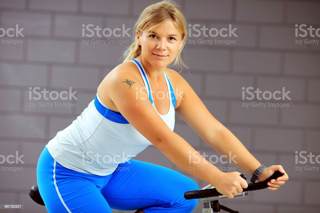 Portrait of a girl training on exercise bike. stock photo