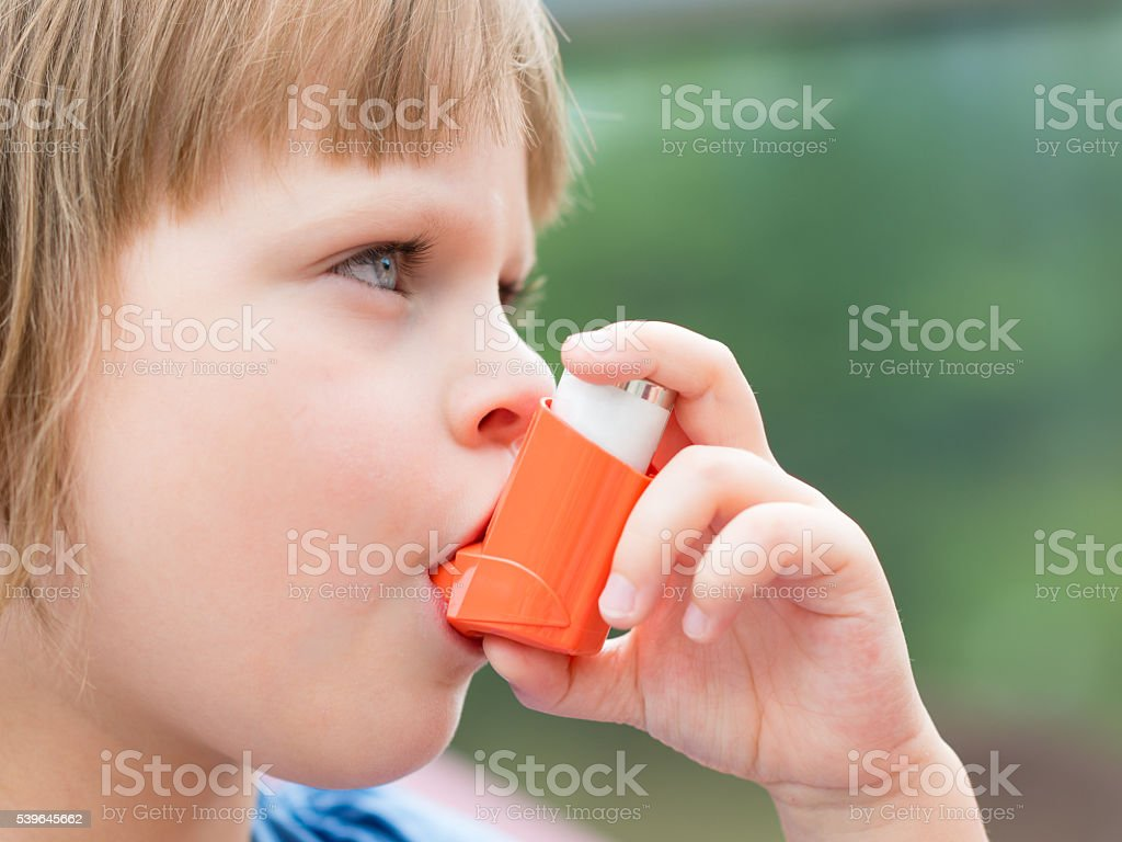Portrait of a girl using asthma inhaler outdoors stock photo