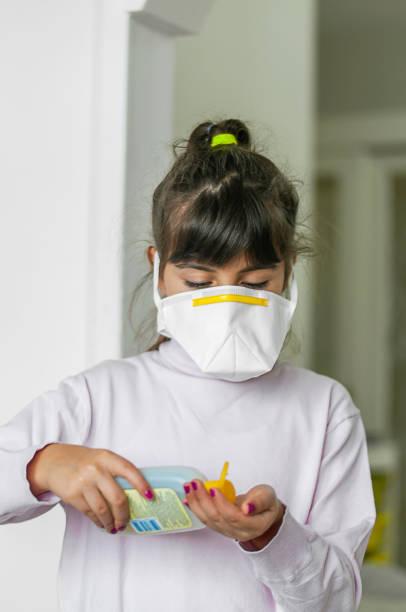 Porträt eines Mädchens, das eine Schutzmaske mit Köln trägt – Foto