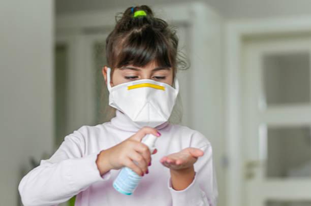 Porträt eines Mädchens, das eine Schutzmaske mit Handdesinfektionsmittel trägt – Foto
