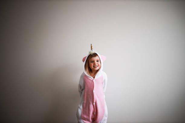 portrait of a girl wearing unicorn pyjama - unicorn bed imagens e fotografias de stock