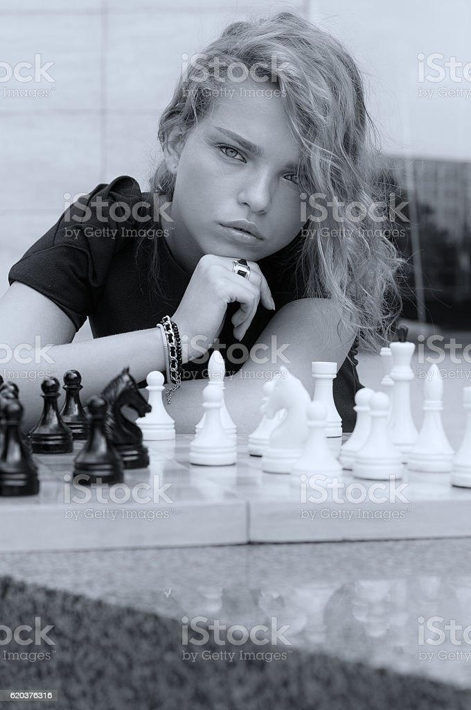 Portrait of a girl who looks at the chessboard foto de stock royalty-free