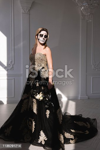 512061362istockphoto Portrait of a girl with a make-up dead man on Halloween. 1135291214