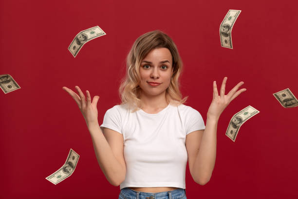 portrait of a girl with curly blond hair dressed in a white t-shirt standing on a red background. happy model throws american dollars expressing emotion of success - throw money away stock pictures, royalty-free photos & images
