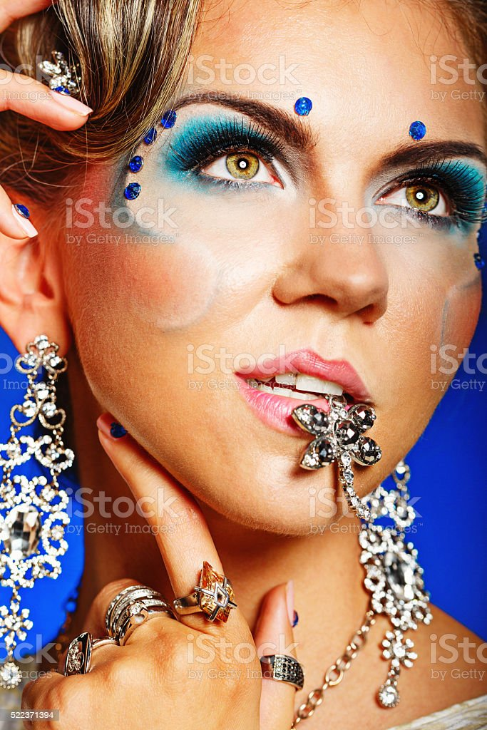 Portrait of a girl with face art, jewelry and hairstyle. stock photo