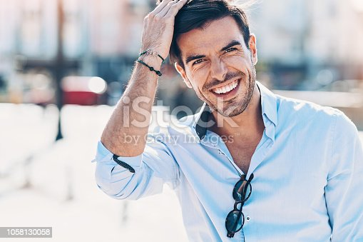 Happy young man walking outdoors in the city